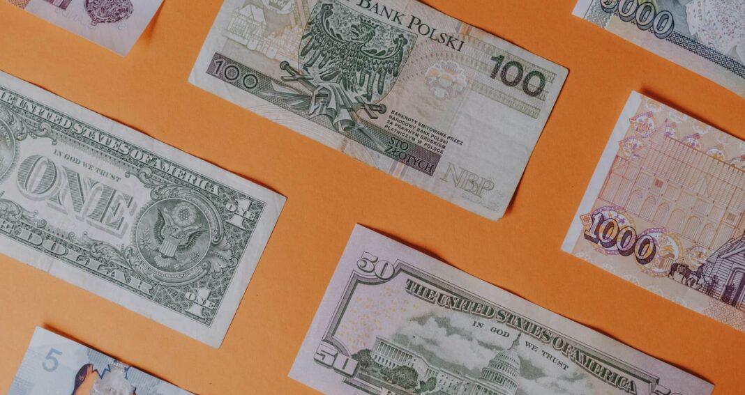 Rozłożone banknoty na pomarańczowym tle, w tym sto złotych, jeden dolar, pięćdziesiąt dolarów.
